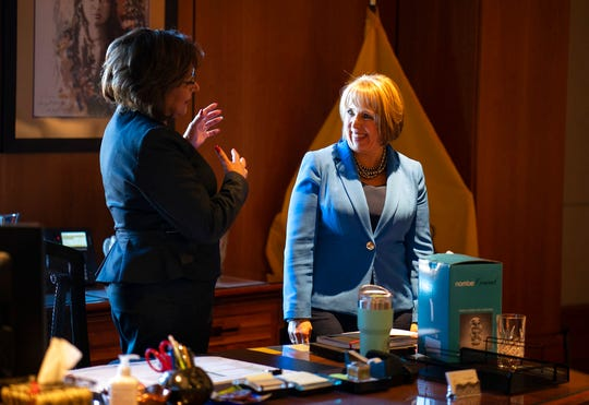 New Mexico Gov. Susana Martinez, left, and U.S. Rep. Michelle Lujan Grisham, who was elected Tuesday as the state's next governor, talk about memorabilia surrounding the Governor's desk during a meeting at the State Capitol in Santa Fe, N.M., on Friday, Nov. 9, 2018. Martinez, a Republican and the state's first female governor, has served two consecutive terms. Lujan Grisham, a Democrat, will take office Jan. 1, 2019.