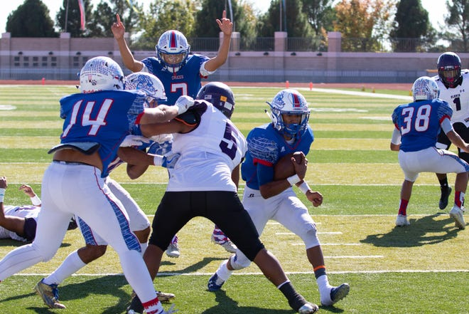 Las Cruces quarterback Marcos Lopez calls the touchdown as Johnny Terrazas crosses the goal line against Clovis Saturday at the Field of Dreams.