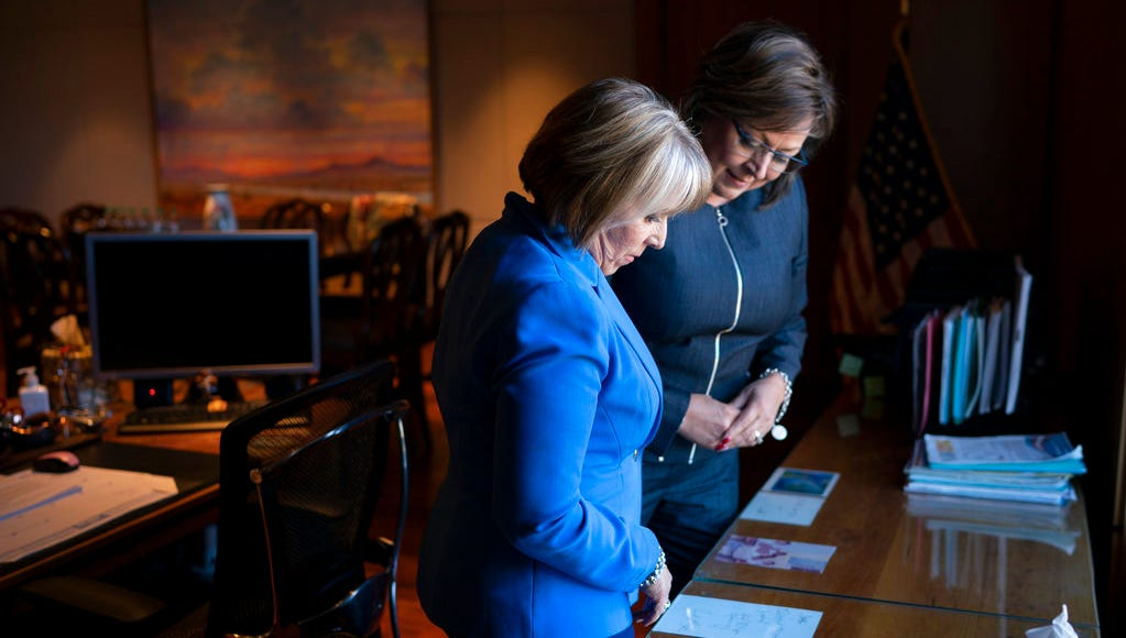New Mexico Gov. Susana Martinez, right, and U.S. Rep. Michelle Lujan Grisham, who was elected Tuesday as the state's next governor, talk about memorabilia surrounding the Governor's desk during a meeting at the State Capitol in Santa Fe, N.M., on Friday, Nov. 9, 2018. Martinez, a Republican and the state's first female governor, has served two consecutive terms. Lujan Grisham, a Democrat, will take office Jan. 1, 2019.