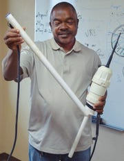 New Mexico State University agricultural researcher Koffi Djaman looks at a soil moisture probe being used at NMSU's Agricultural Science Center at Farmington to determine if irrigation water reaches plant roots.