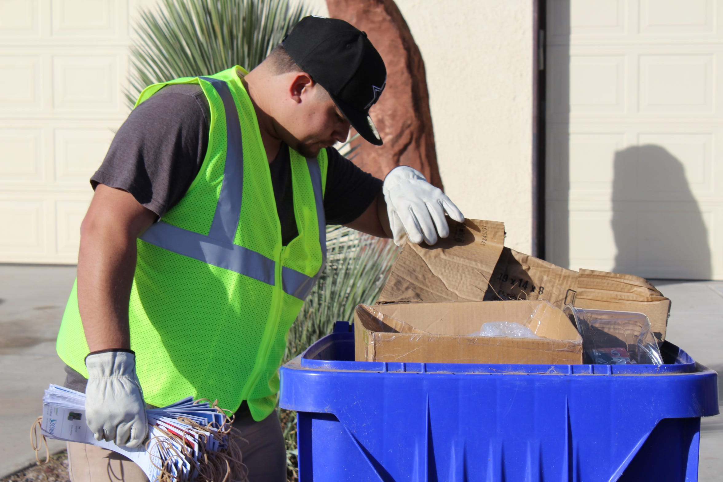 "Recycling Auditor Nicolas Jacques peers into the blue recycling bin. Does it get an ""Oops!"" tag or a ""Thank you!"" tag?"