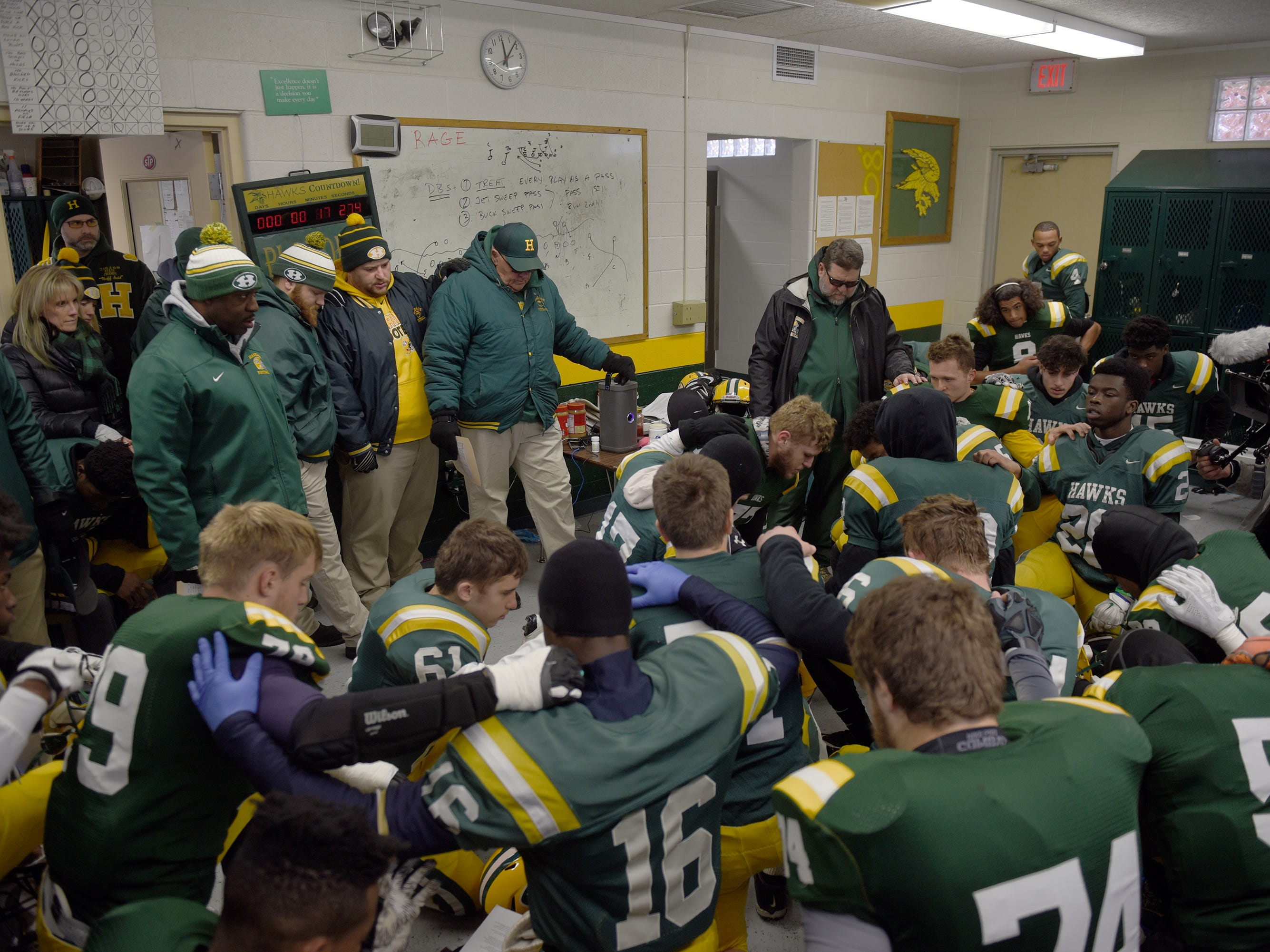 Farmington Harrison Head Coach John Herrington and his team prepare for the start to the last game of the Harrison football program as the Hawks lost in the Division 4 regional finals 21-14 to Chelsea at Buller Field Nov. 10, 2018.