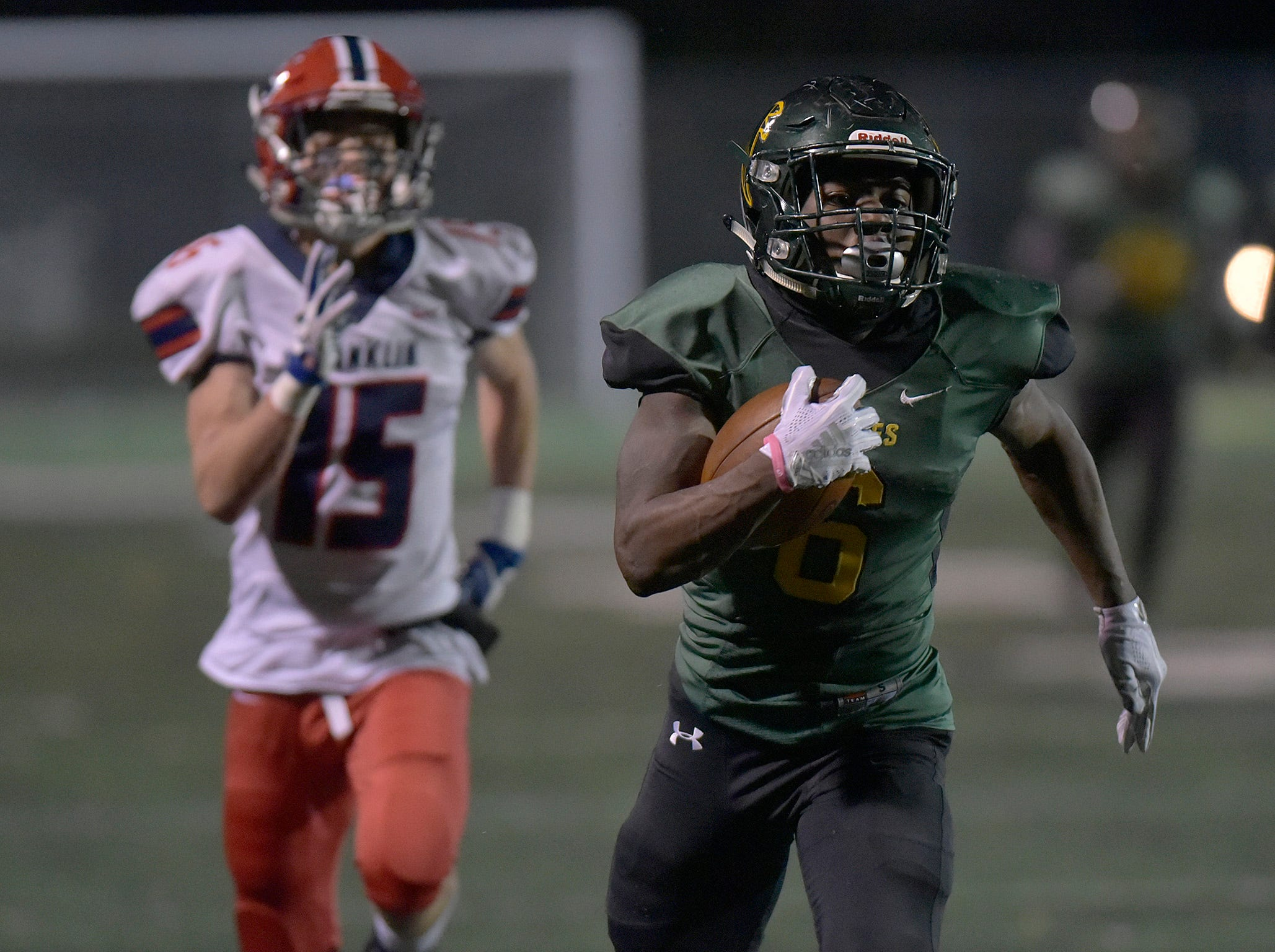 Birmingham Groves RB/FS Damonte McCurdy (6) gains yards, followed by Livonia Franklin's DB/SL Kyle Hetu.