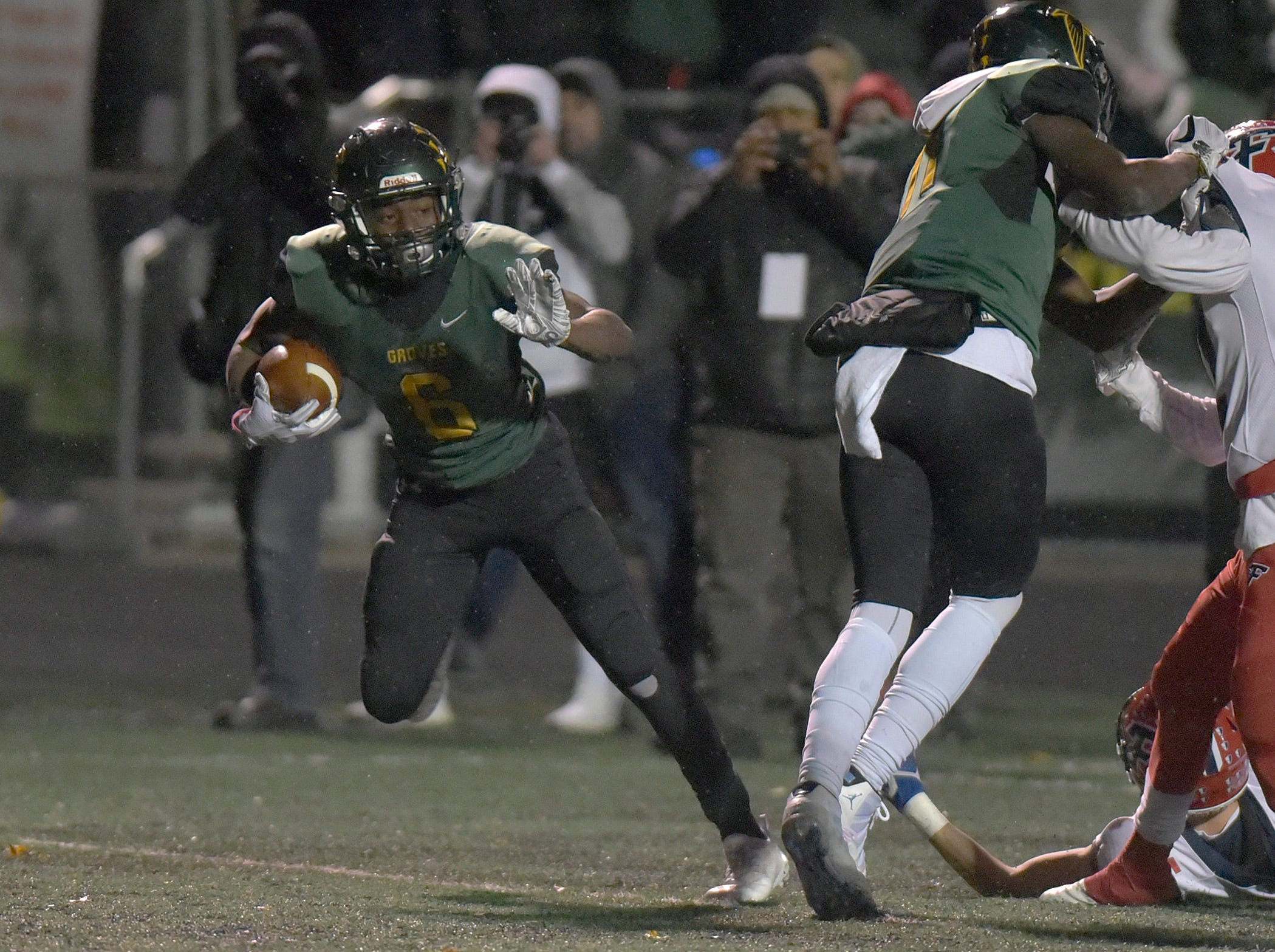 Birmingham Groves RB/FS Damonte McCurdy (6) looks over his shoulder on his way to a Groves touchdown.