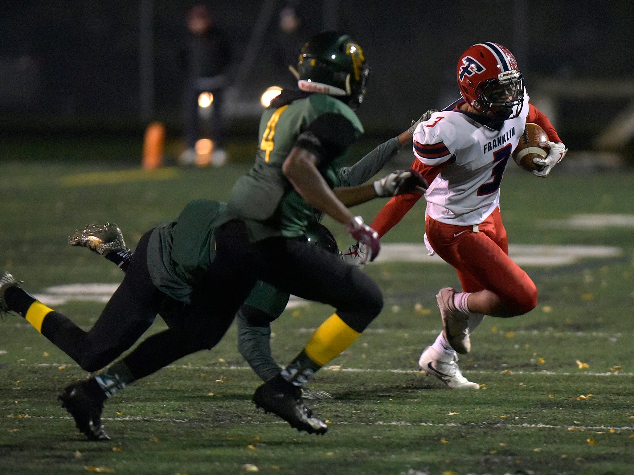 Franklin defensive back KJ Worthy tries to evade Groves defenders.