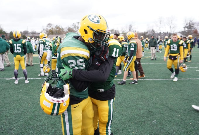 Farmington Harrison SE/DB T'Sean Sample (25) and Alan Robertson (11) hug after the Hawks lose in the Division 4 regional final played at Buller Field Nov. 10, 2018