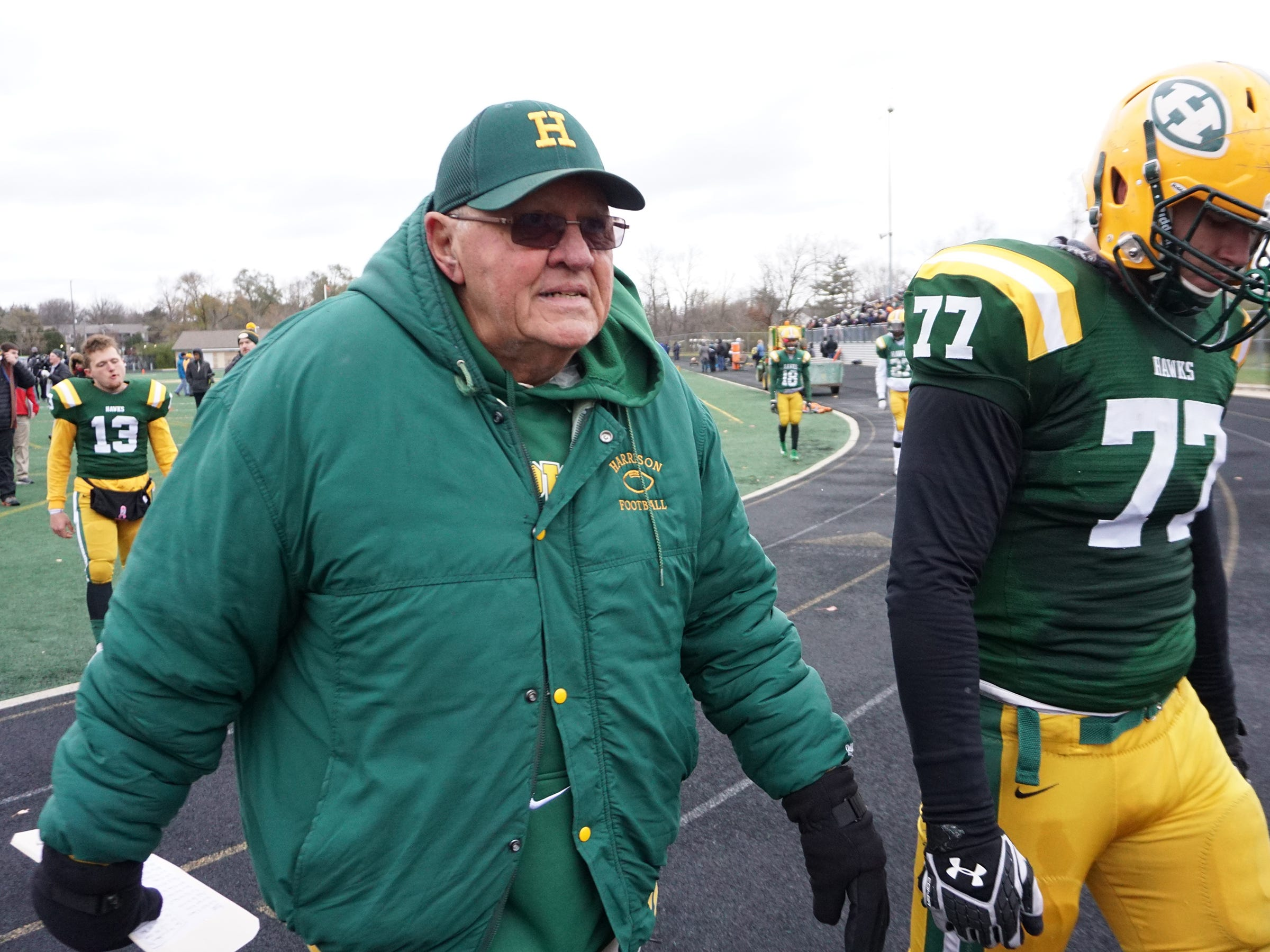 Farmington Harrison Head Coach John Herrington walks off the field with Maverick Hansen (77) after losing 21-14 to Chelsea  in the Division 4 regional final played at Buller Field Nov. 10, 2018