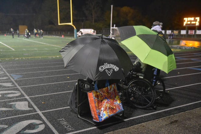A constant drizzle and cold temps can't keep fans away from the regional football game between Livonia Franklin and Birmingham Groves.