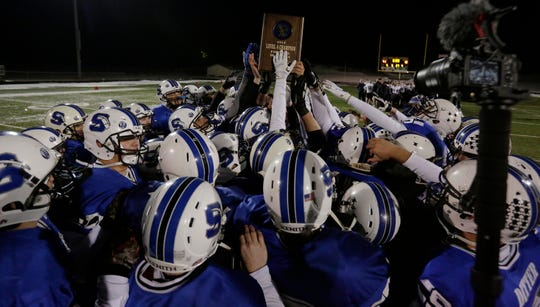 Springs hoists the WIAA Division 5 semifinal trophy Friday after defeating Lake Country Lutheran 41-12.