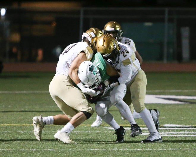 Eduardo Enriquez is unable to get past Xavier Prep defenders. The Xavier Prep varsity football team won Friday's CIF  playoff game against Nogales by a score of 24-21.