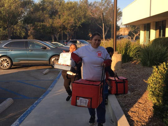 Salvation Army volunteers bring bagels and burritos to the Thousand Oaks Teen Center, where evacuees are staying during the Woolsey Fire. The Salvation Army says it needs contributions in order to keep helping evacuees.