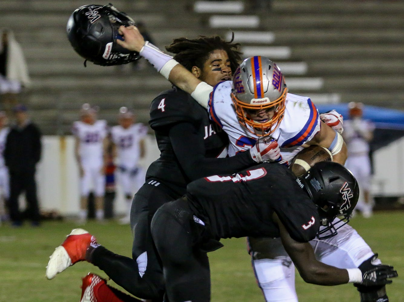 West Florida Tech's Antarrius Moultrie (4) has his helmet ripped off by Jacksonville Bolles' CJ Grimes (22) as teammate Keyshawn Swanson (3) comes in to help with the tackle in the Region 1-5A quarterfinal game at Woodham Middle School on Friday, November 9, 2018.