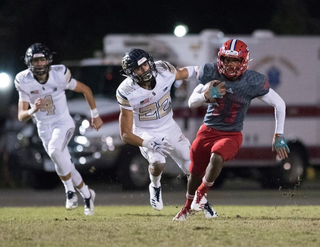 Pine Forest High School's Anwar Lewis, (No. 25) finds daylight and sprints upfield as Gulf Breeze High School's Christian Murphy, (No. 22) gives chase during Friday night's playoff game.