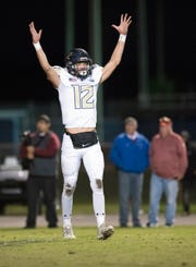 Gulf Breeze High School's Cooper Harris, (No. 12) signals the team's first touchdown of the game during Friday night's playoff against Pine Forest High School.