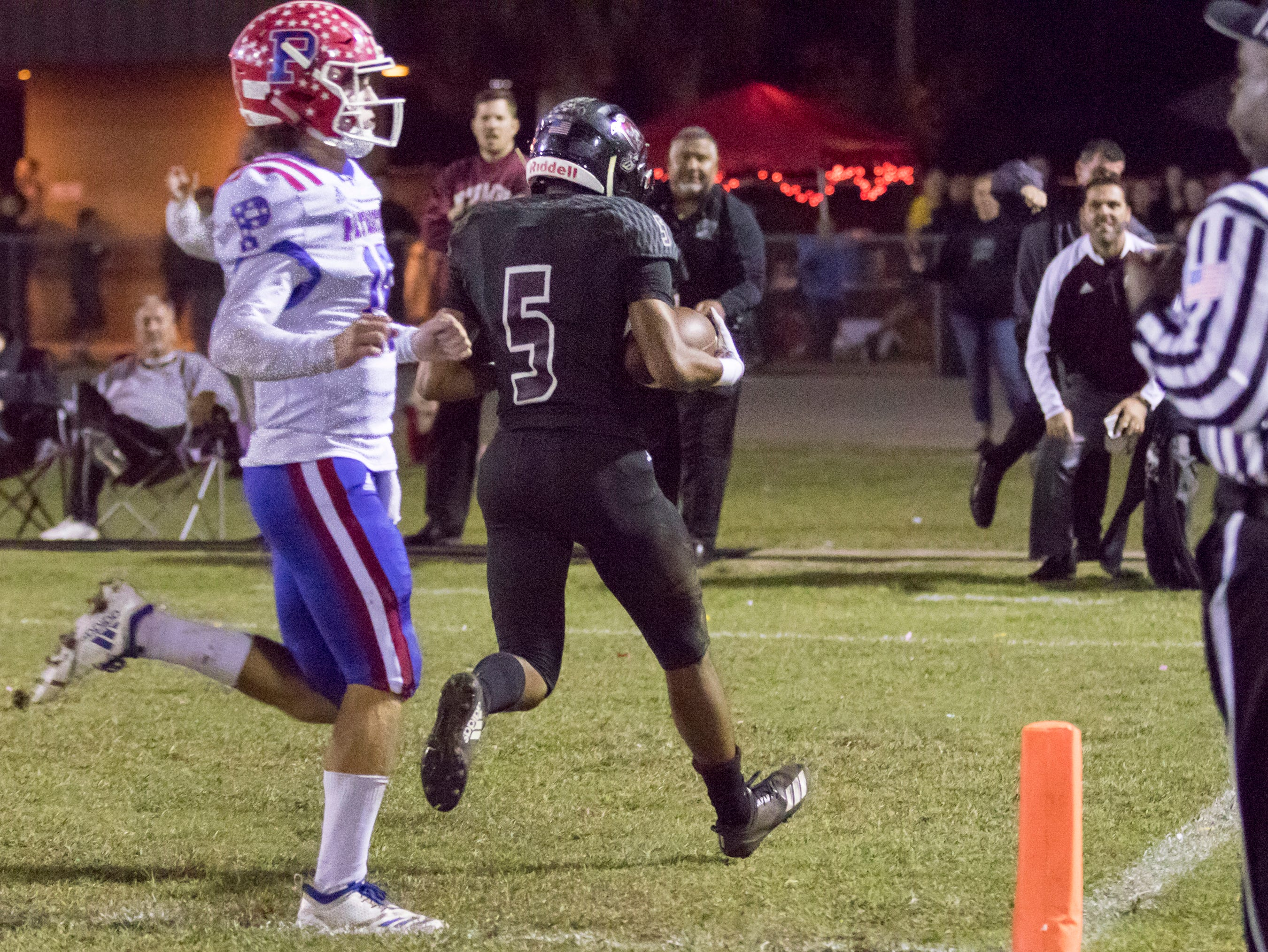 Dante Wright (5) runs for a touchdown a and a 10-0 Raiders lead after adding the extra point during the Pace vs Navarre playoff football game at Navarre High School on Friday, November 9, 2018.