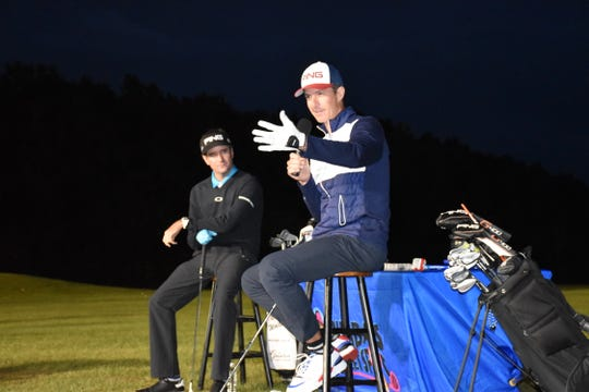 Bubba Watson listens as his long-time caddie Ted Scott provides insight on Watson's golf skills during a free clinic Friday at the Pensacola Golf Center