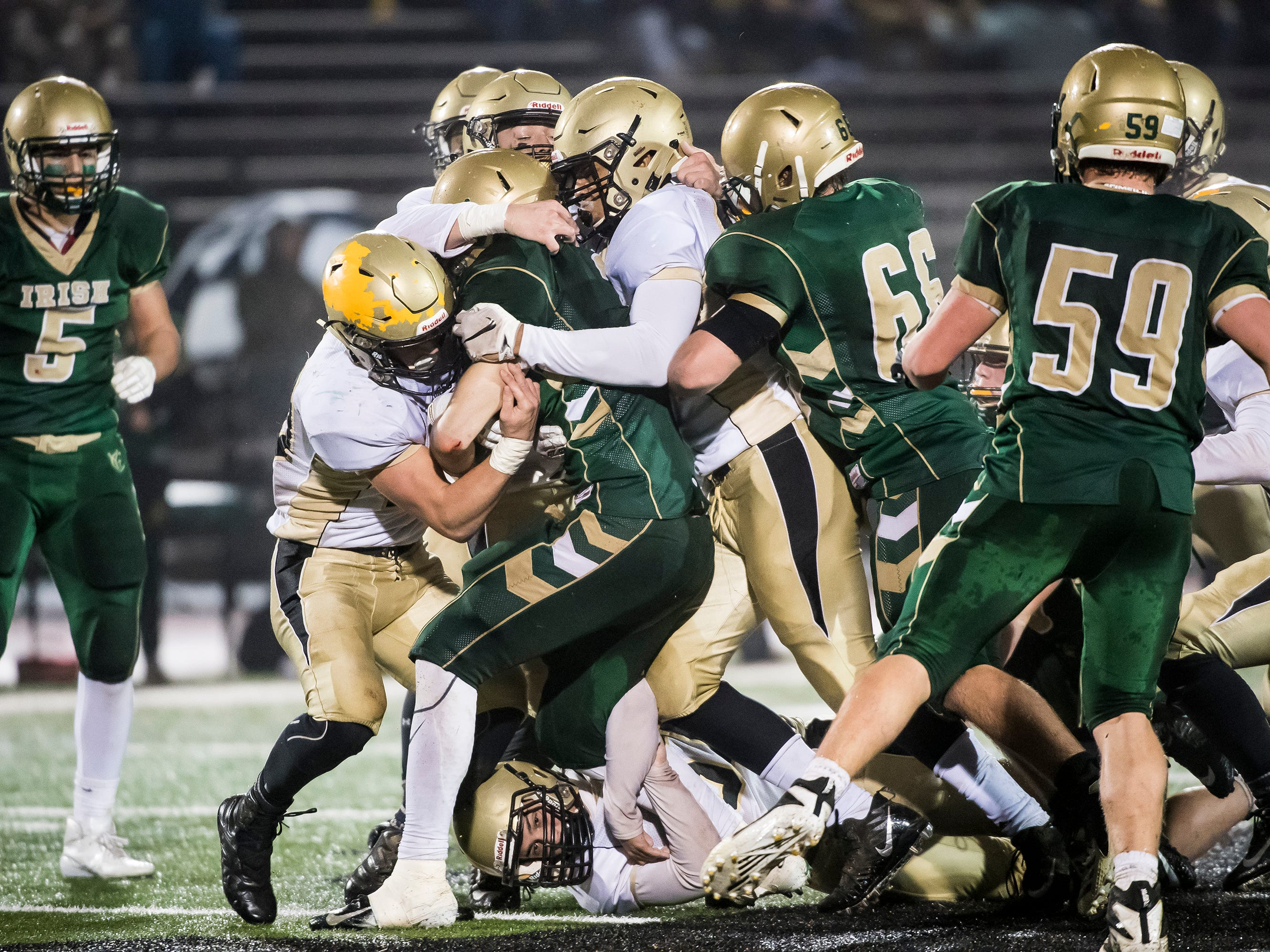 A host of Delone Catholic players tackle York Catholic's Cole Witman during the PIAA District 3 Class 2A championship game at South Western High School on Friday, November 9, 2018. The Squires fell 28-21 in overtime.