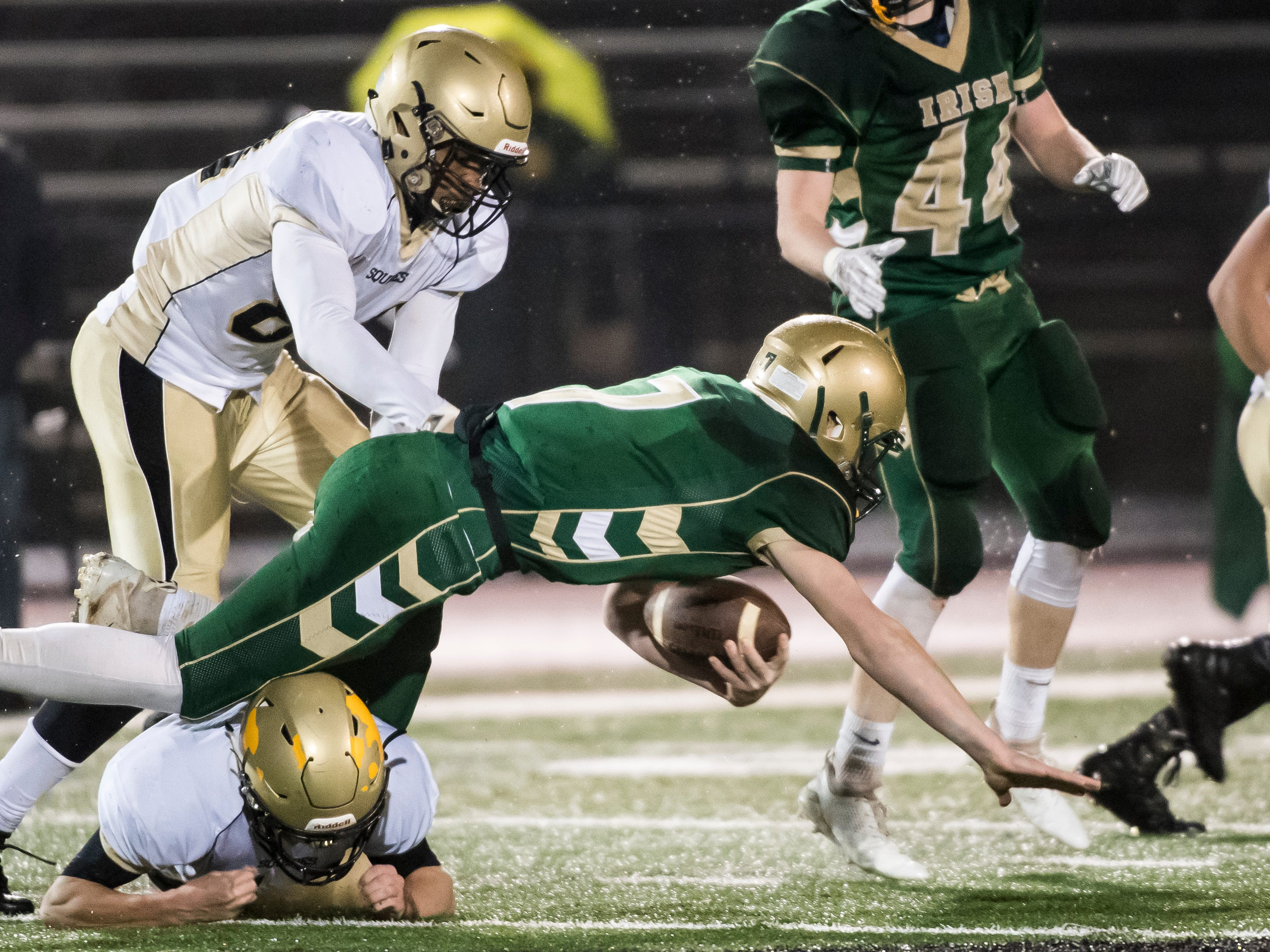 York Catholic's Mitchell Galentine is tripped up by a Delone Catholic defender during the PIAA District 3 Class 2A championship game at South Western High School on Friday, November 9, 2018. The Squires fell 28-21 in overtime.