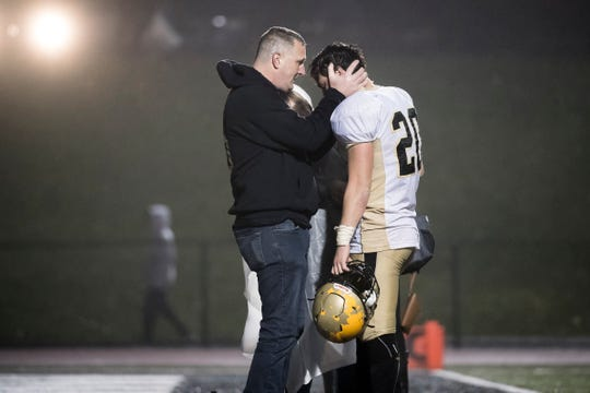 Delone Catholic's Tyler Monto is consoled by family members after the Squires fell to York Catholic 28-21 in overtime in the PIAA District 3 Class 2A championship game at South Western High School on Friday, November 9, 2018.