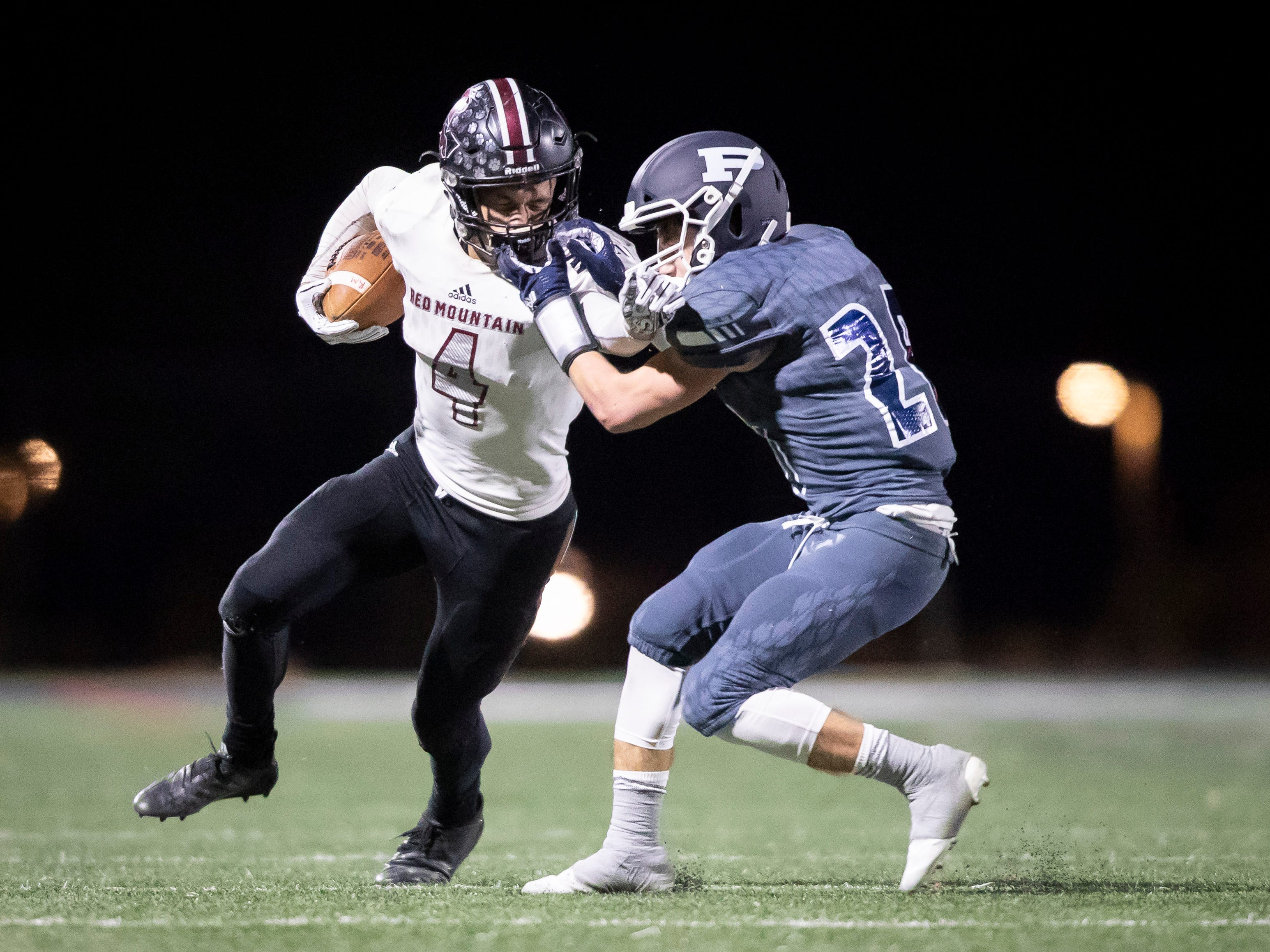 Junior running back Ramses Rivera Ii (4) of the Red Mountain Mountain Lions runs the ball against junior center Jack Havener (28) of the Pinnacle Pioneers during the playoff game at Pinnacle High School on Friday, November 9, 2018 in Phoenix, Arizona. #azhsfb