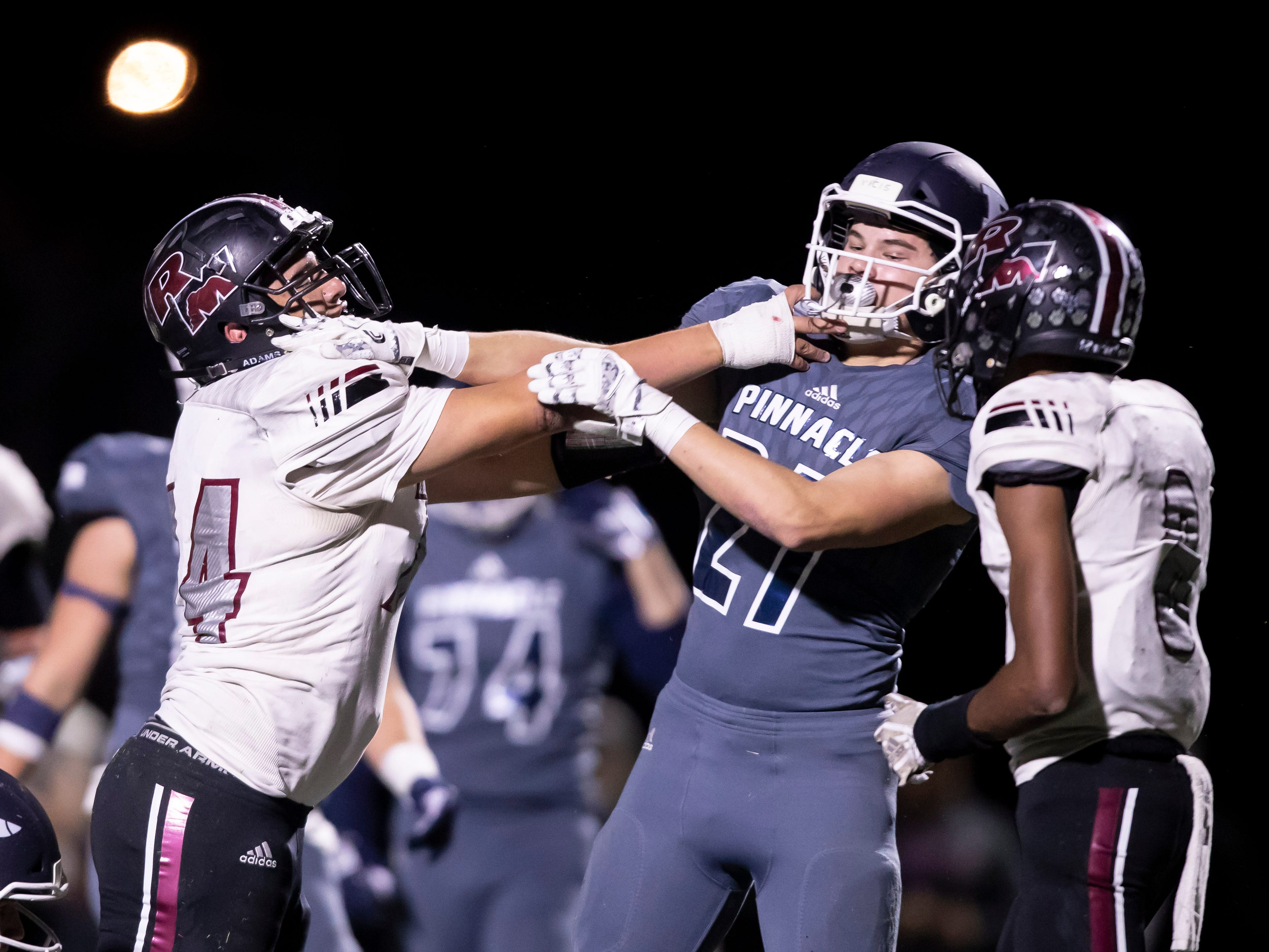 Senior guard Francisco Saucedo (74) of the Red Mountain Mountain Lions and junior linebacker Cooper Dirck (27) of the Pinnacle Pioneers shove each other following a play during the playoff game at Pinnacle High School on Friday, November 9, 2018 in Phoenix, Arizona. #azhsfb