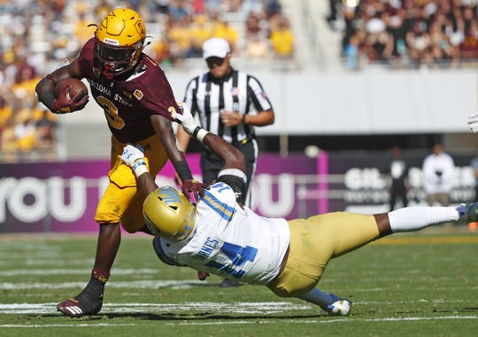 ASU's Eno Benjamin (3) stiff-arms UCLA's Krys Barnes (14) during the first half at Sun Devil Stadium in Tempe, Ariz. on November 10, 2018.