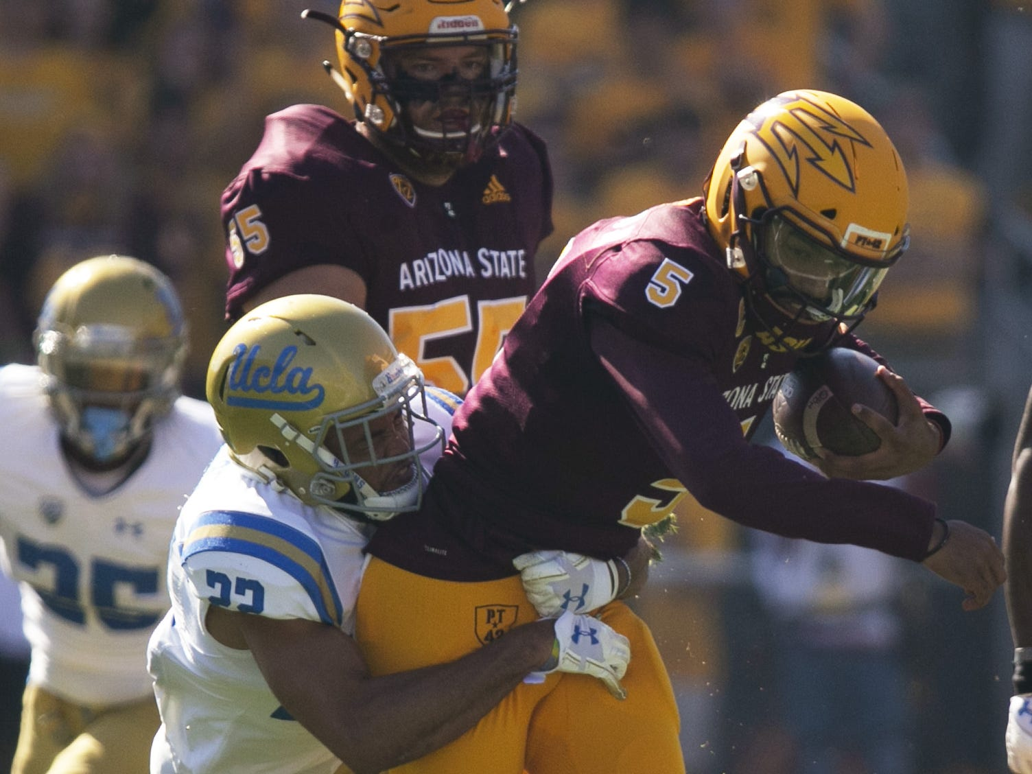 ASU quarterback Manny Wilkins carries the ball as UCLA defensive back Nate Meadors makes the tackle during the first quarter of the PAC-12 college football game at Sun Devil Stadium in Tempe on Saturday, November 10, 2018.