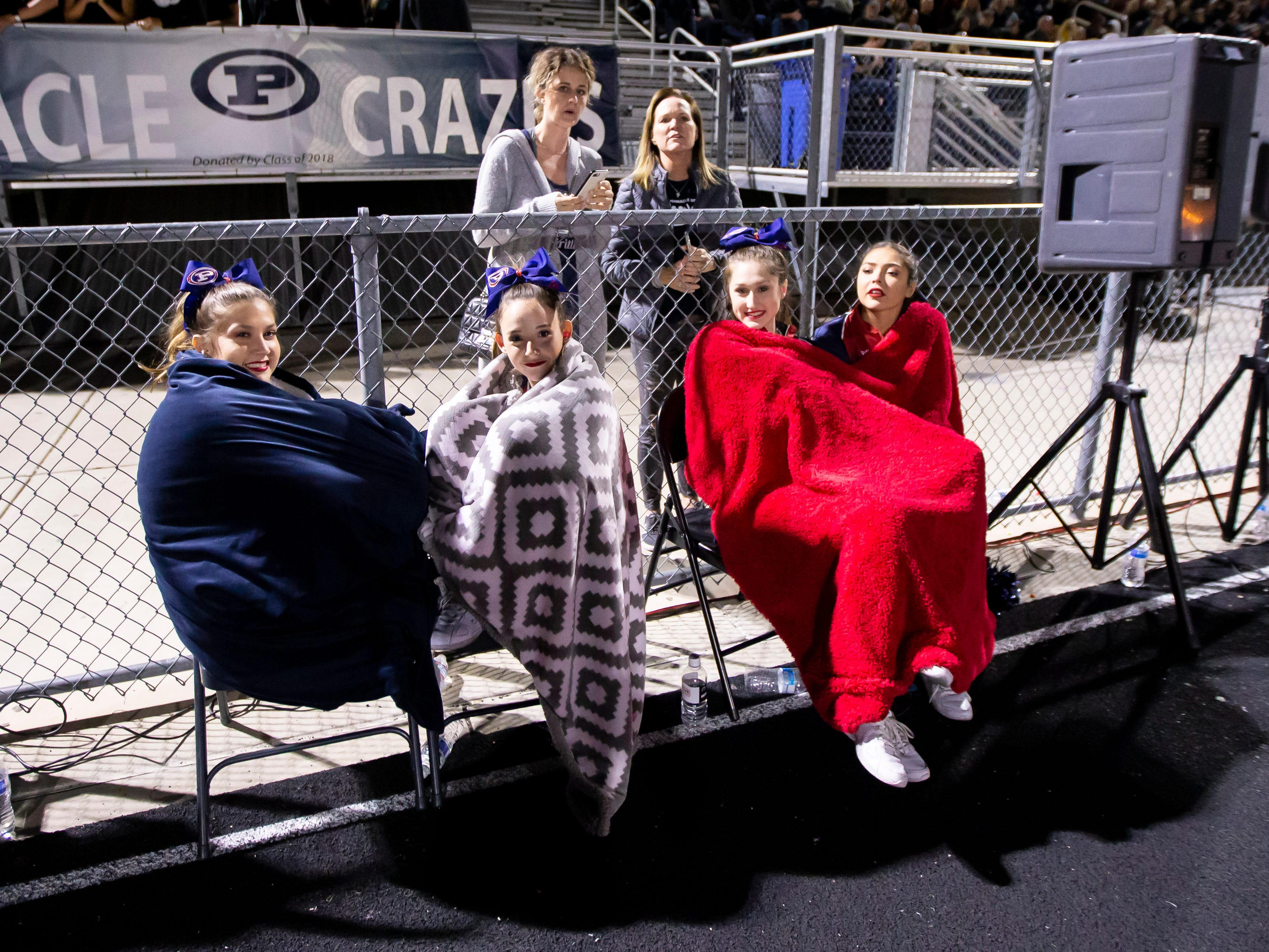 Pinnacle cheerleaders sit with blankets on a chilly night during the playoff game against the Red Mountain Mountain Lions at Pinnacle High School on Friday, November 9, 2018 in Phoenix, Arizona. #azhsfb