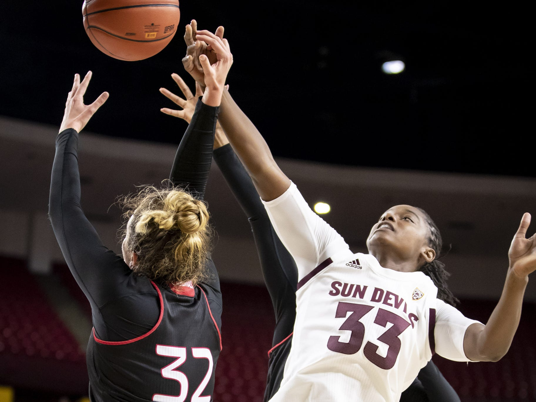 Forward Olivia Noah (32) of the Incarnate Word Cardinals (L)  and center Charnea Johnson-Chapman (33) of the Arizona State Sun Devils (R) reach for a rebound at Wells Fargo Arena on Tuesday, November 6, 2018 in Tempe, Arizona.