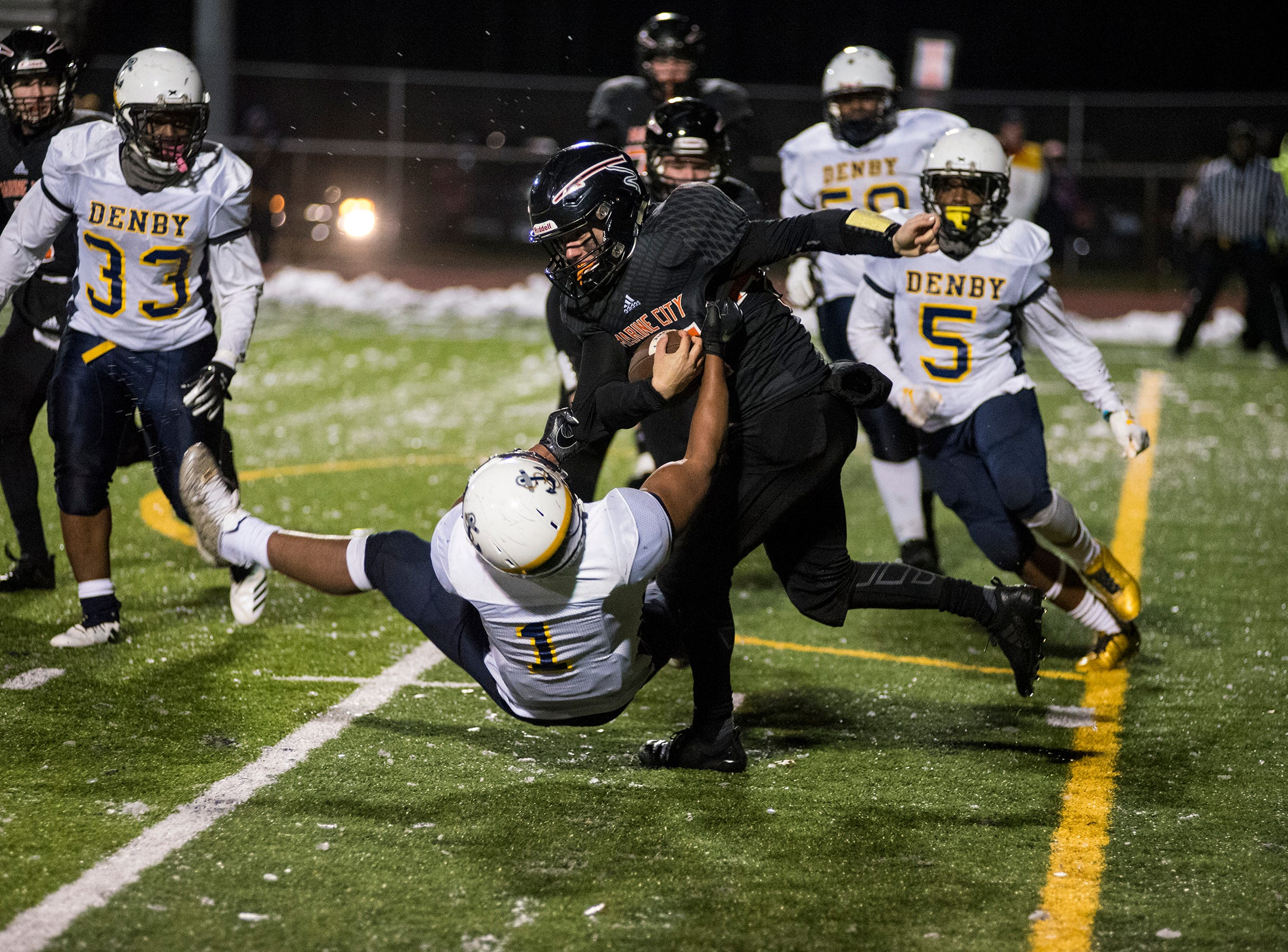 Detroit Denby Tech's Jamari Griffin (1) tackles Marine City High School's Aren Sopfe during the MHSAA Division 5 regional championship game Friday, Nov. 9, 2018 at East China Stadium.