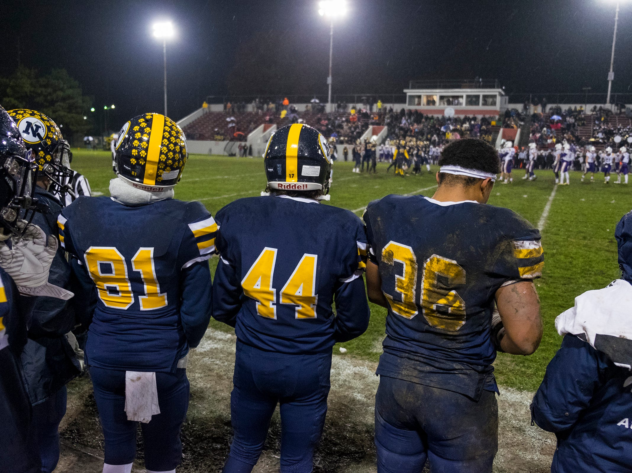 Wet and muddy players from Port Huron Northern High School watch the MHSAA Division 2 regional championship game against Warren De La Salle from the sidelines Friday, Nov. 9, 2018 at Memorial Stadium.