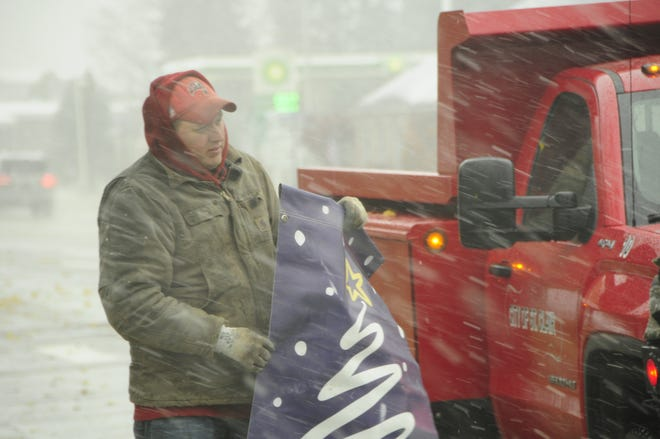 Snow flies Friday as Craig Melms of the St. Clair DPW carries a holiday banner. There is a  possibility of snow today.