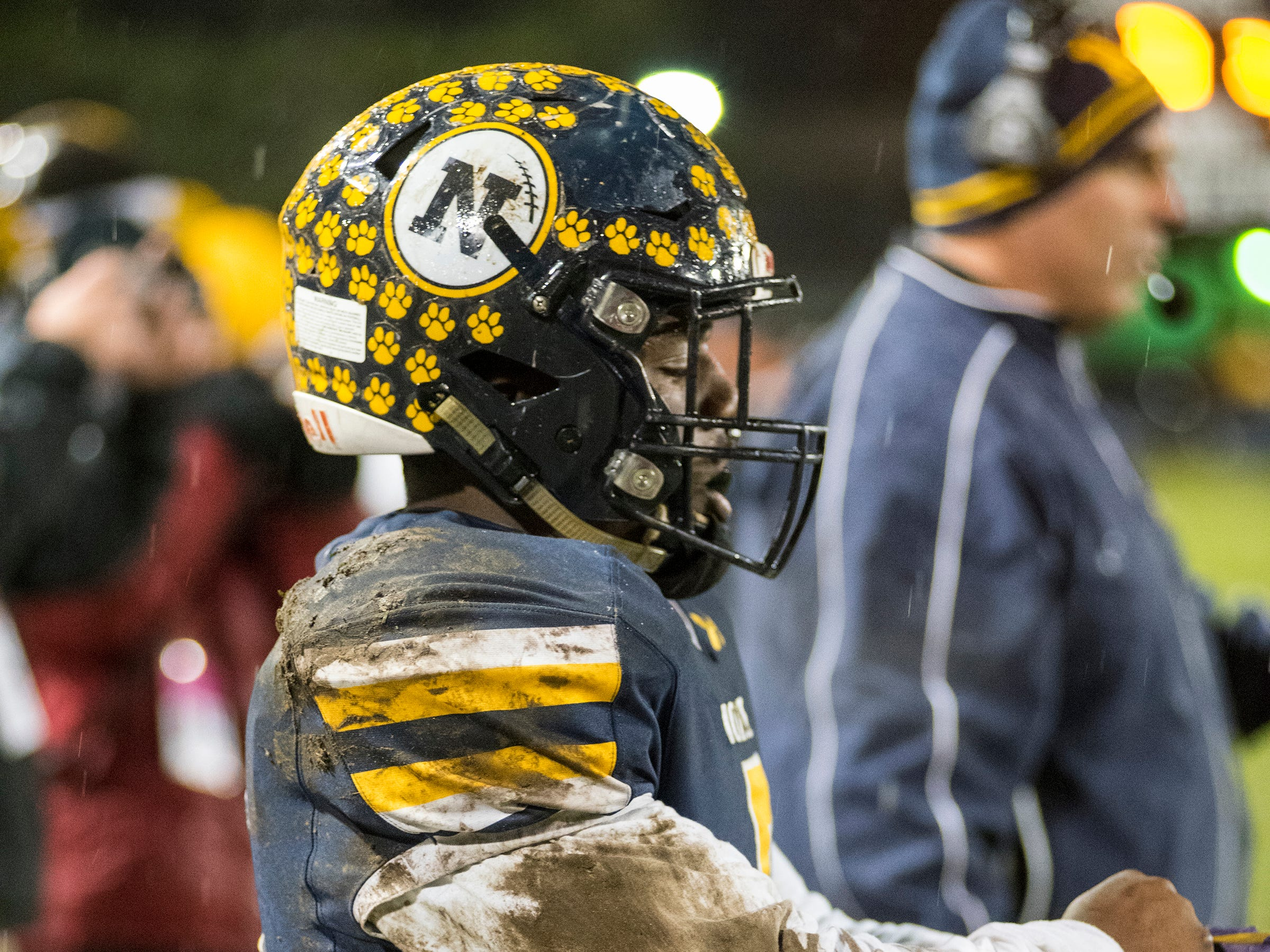 Port Huron Northern High School's John Young slips his gloves back on before playing during the first quarter of the MHSAA Division 2 regional championship game against Warren De La Salle Friday, Nov. 9, 2018 at Memorial Stadium.