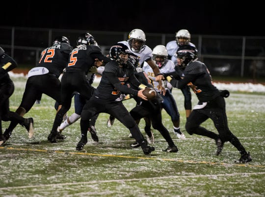 Marine City High School quarterback Colby Walker (9) hands off the football to running back Aren Sopfe during the MHSAA Division 5 regional championship game against Detroit Denby Tech Friday, Nov. 9, 2018 at East China Stadium.
