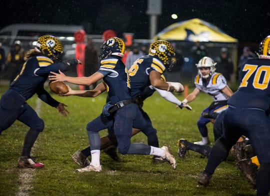 Port Huron Northern High School quarterback Seth Klink (center) hands off the football during the first quarter of the MHSAA Division 2 regional championship game against Warren De La Salle Friday, Nov. 9, 2018 at Memorial Stadium.
