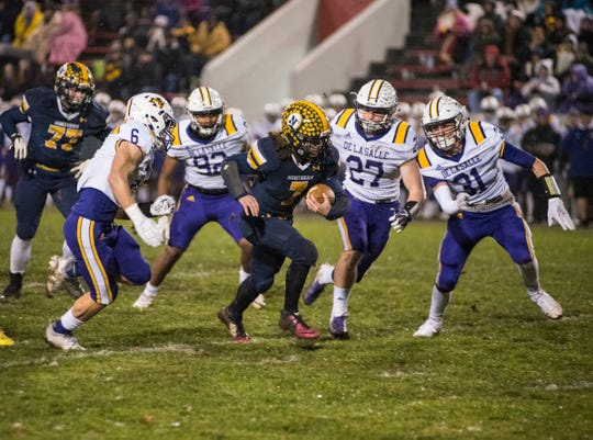 Port Huron Northern High School running back Theo Ellis (7) runs the football through players from Warren De La Salle during the MHSAA Division 2 regional championship game Friday, Nov. 9, 2018 at Memorial Stadium.