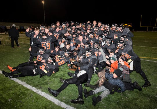 The Marine City High School football team pose with the MHSAA Division 5 regional championship trophy after defeating Detroit Denby Tech 40-32 in double overtime Friday, Nov. 9, 2018 at East China Stadium.