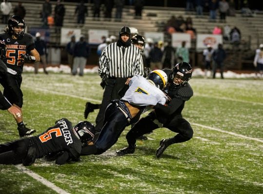Marine City High School defensive back Derek Landis (right) tackles Detroit Denby Tech's Tshawn Wilkes during the MHSAA Division 5 regional championship game Friday, Nov. 9, 2018 at East China Stadium.