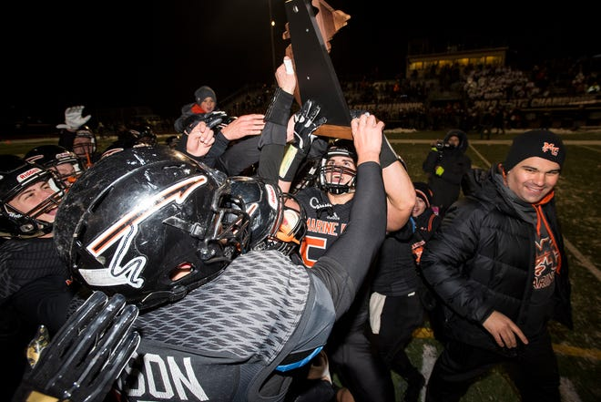 Marine City High School football players celebrate with the MHSAA Division 5 regional championship trophy after defeating Detroit Denby Tech 40-32 in double overtime Friday, Nov. 9, 2018 at East China Stadium.