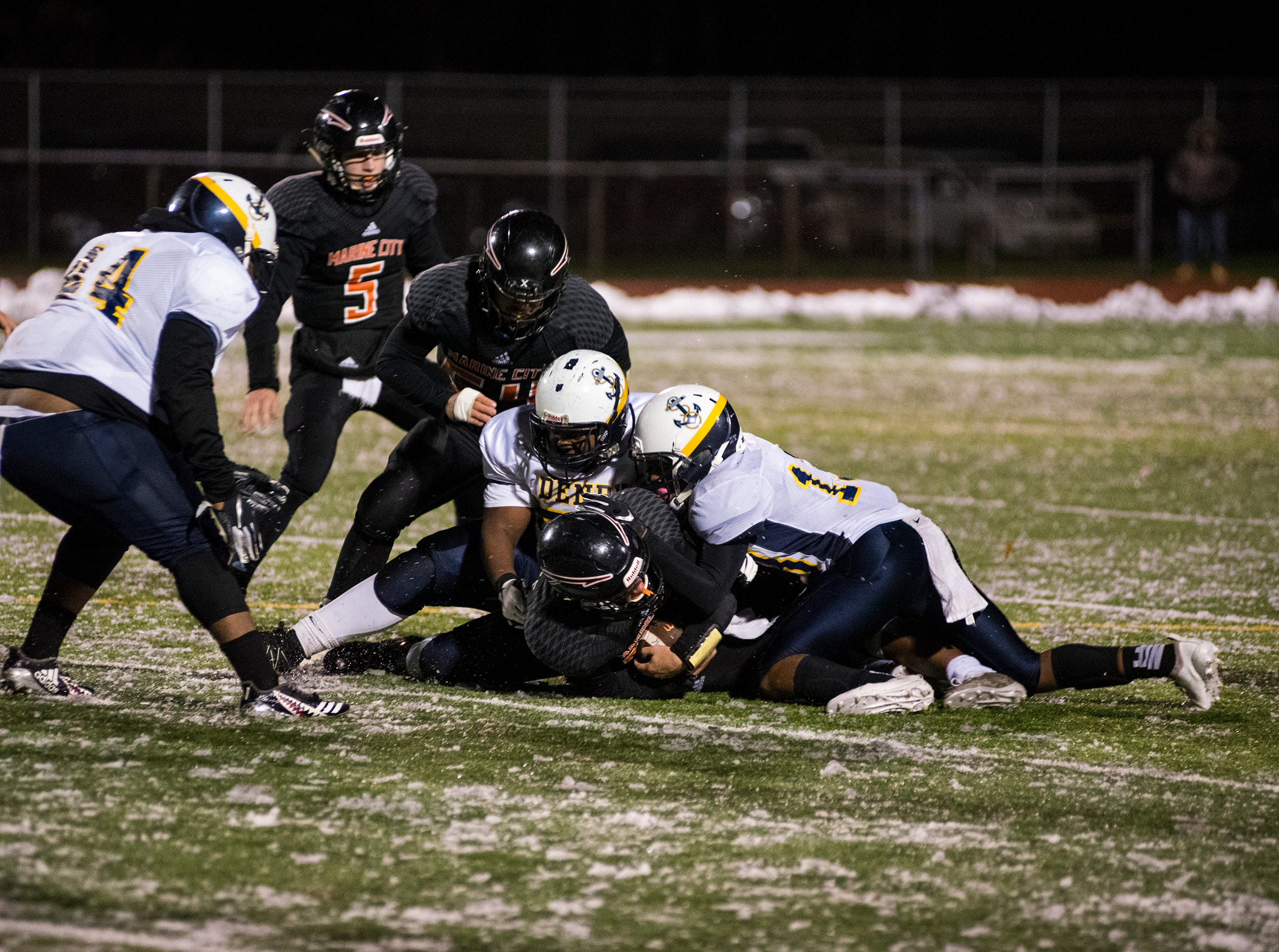 Marine City High School running back Aren Sopfe holds onto the football as two players from Detroit Denby Tech tackle him during the MHSAA Division 5 regional championship game Friday, Nov. 9, 2018 at East China Stadium.