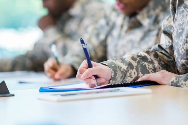 Service members take notes in class while in college.