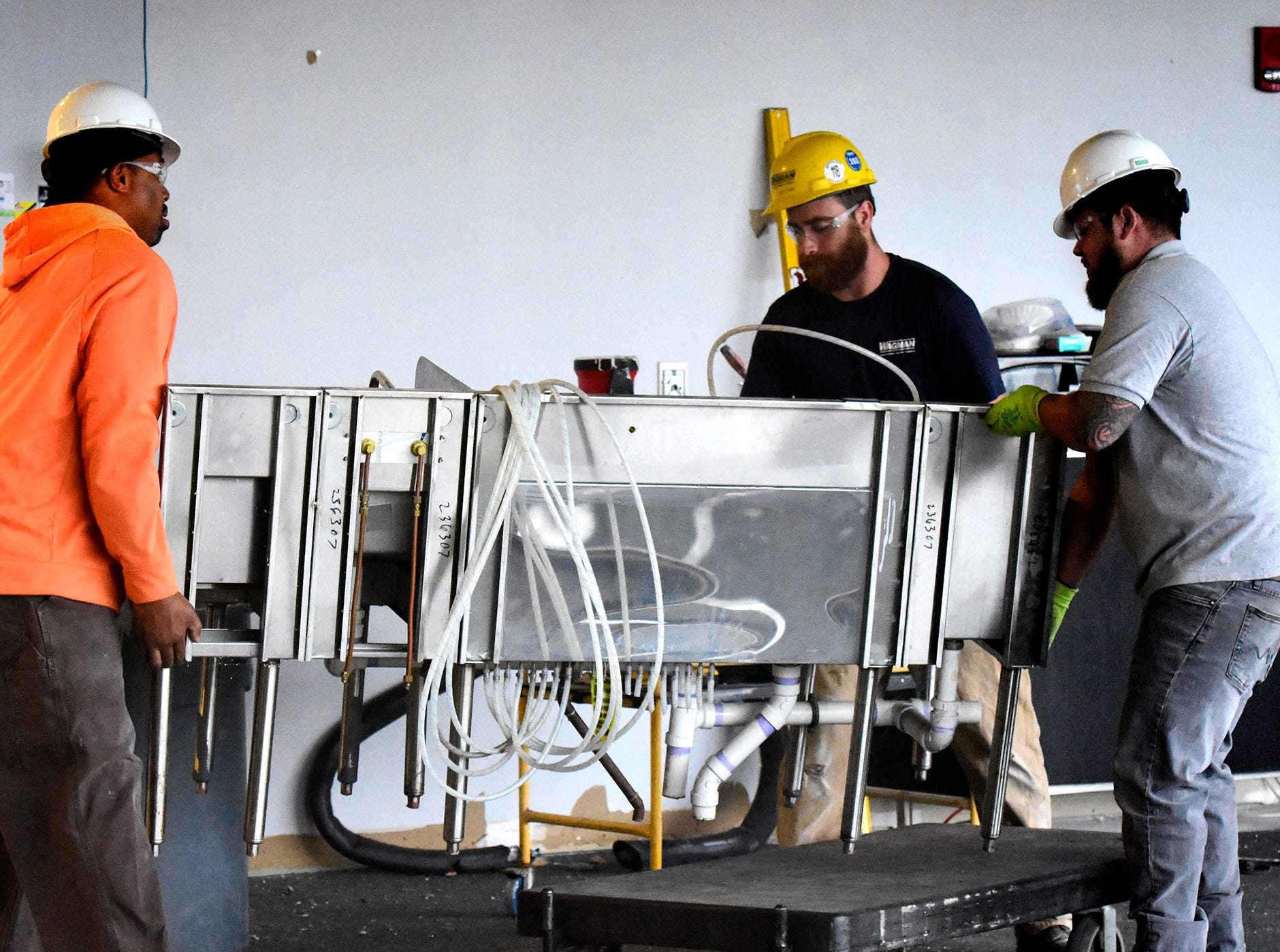 Wagman Construction workers, from left, Kenneth Autry, Jr, Brandon Girard and C.J, Fitch move a bar feature while clearing the former White Room at PeoplesBank Park Friday, Nov. 9, 2018. The room will house the 1741 Club starting in the 2019 season.  Bill Kalina photo