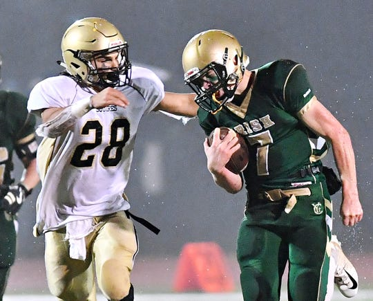 Delone Catholic's Joe Hernandez, left, looks to take down York Catholic's Mitchell Galentine during District 3, Class 2-A football title game action at South Western High School in Hanover, Friday, Nov. 9, 2018. York Catholic would win the game 28-21 in overtime. Dawn J. Sagert photo