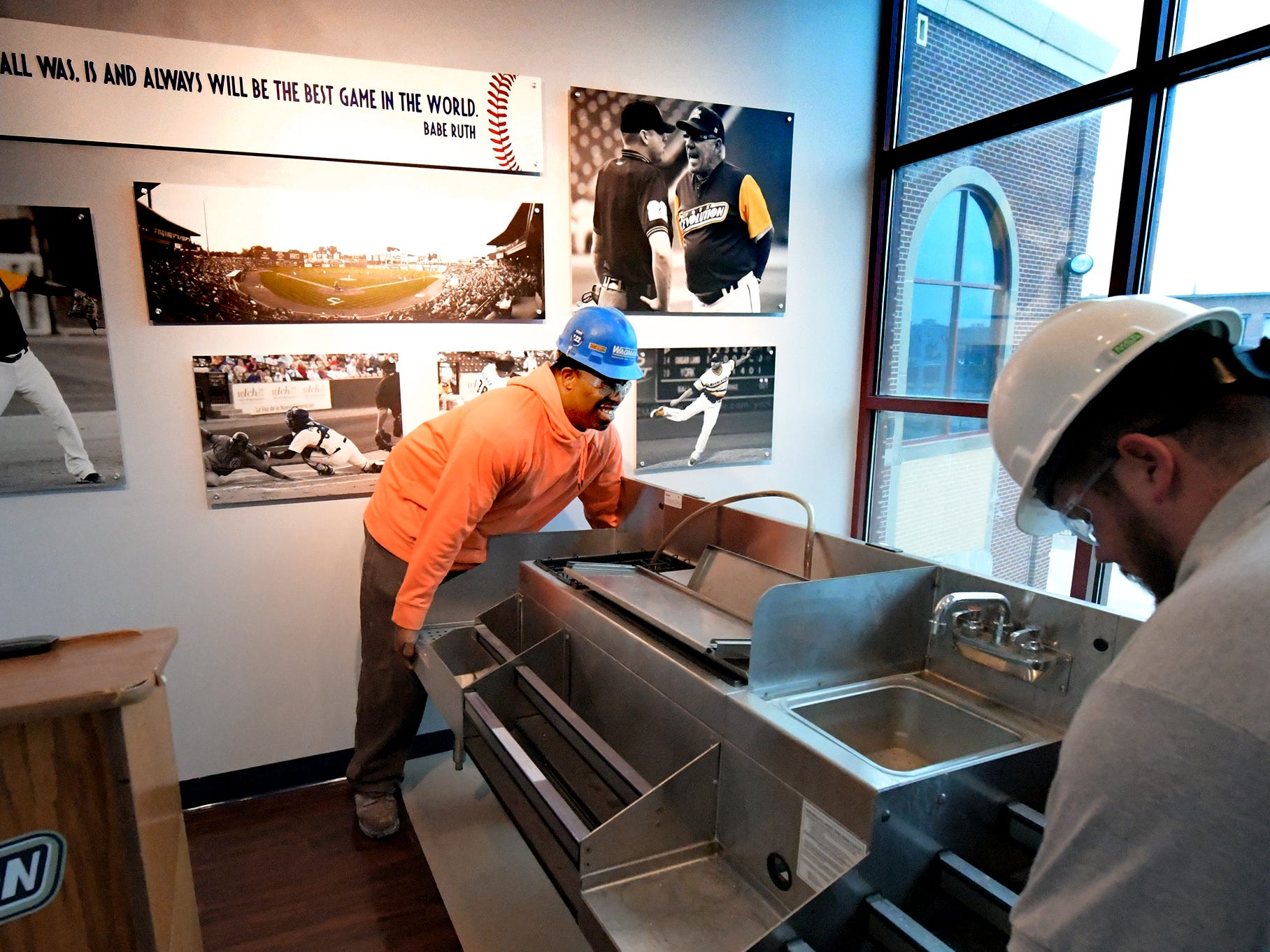 Wagman Construction employees Kenneth Autry, Jr. and C.J. Fitch, right, move a bar fixture from the White Rose Room at PeoplesBank Park Friday, Nov. 9, 2018. The room in being transformed to house the 1741 Club, an all-inclusive dining and drink pass for corporate rental. The club will be available for the 2019 season. Bill Kalina photo