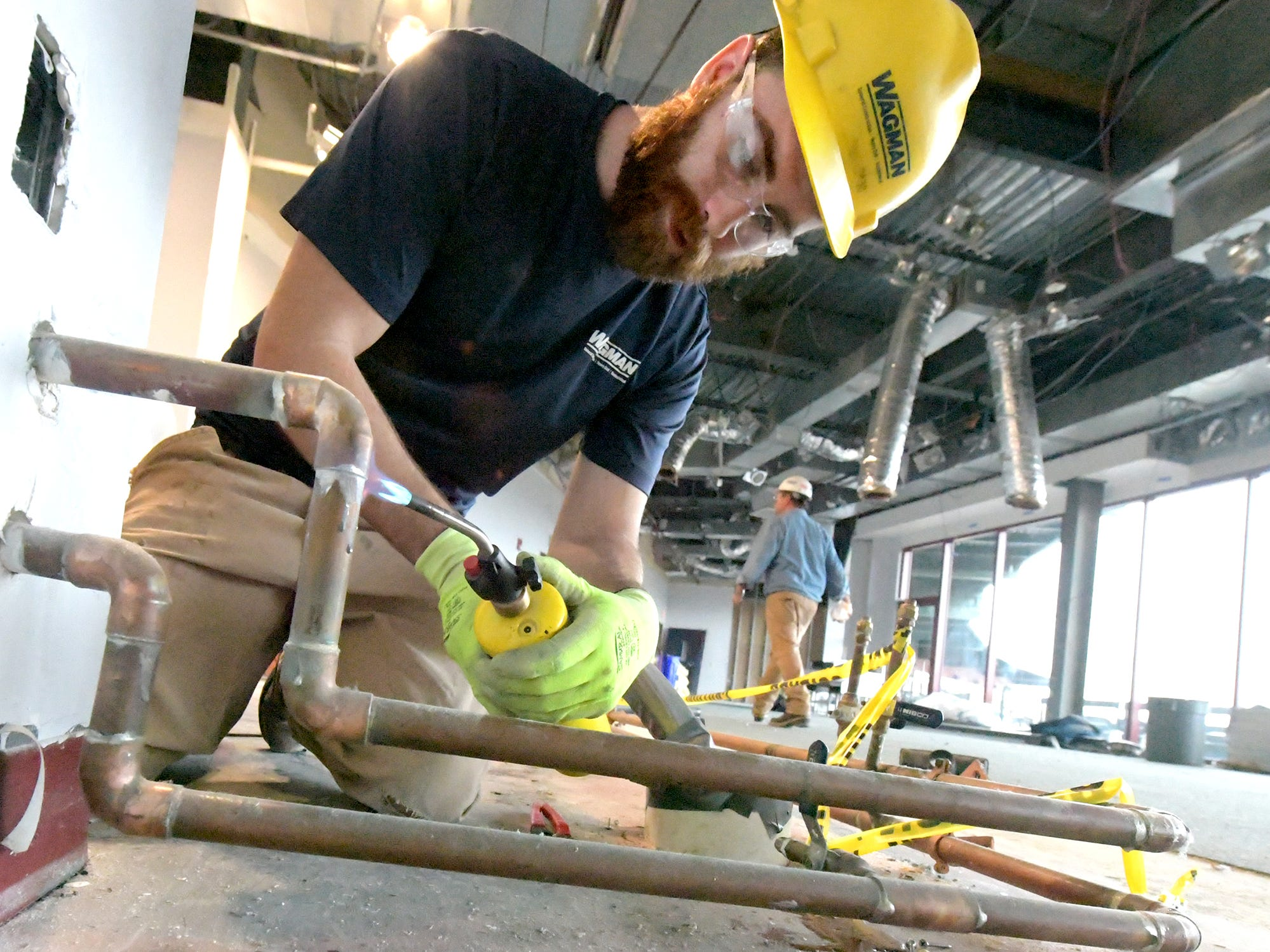 Brandon Girard of Wagman Construction uses a torch to loosen copper water pipe while removing it in the former White Rose Room at PeoplesBank Park Friday, Nov. 9, 2018. The room in being transformed to house the 1741 Club, an all-inclusive dining and drink pass for corporate rental. The club will be available for the 2019 season. Bill Kalina photo