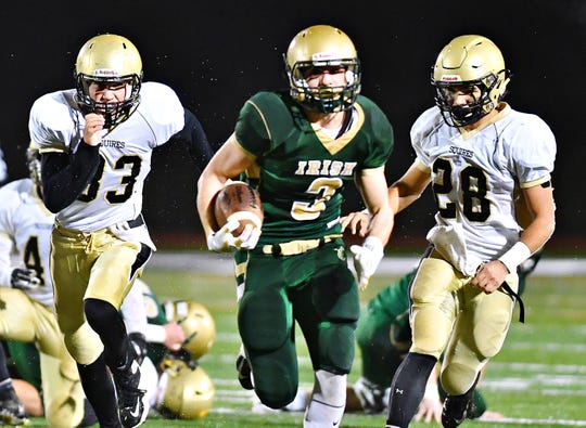 Delone Catholic's Gabe Hernandez, left, and Joe Hernandez, right, work to keep up with York Catholic's Cole Witman as he scores a touchdown during District 3, Class 2-A football title game action against Delone Catholic at South Western High School in Hanover, Friday, Nov. 9, 2018. York Catholic would win the game 28-21 in overtime. Dawn J. Sagert photo