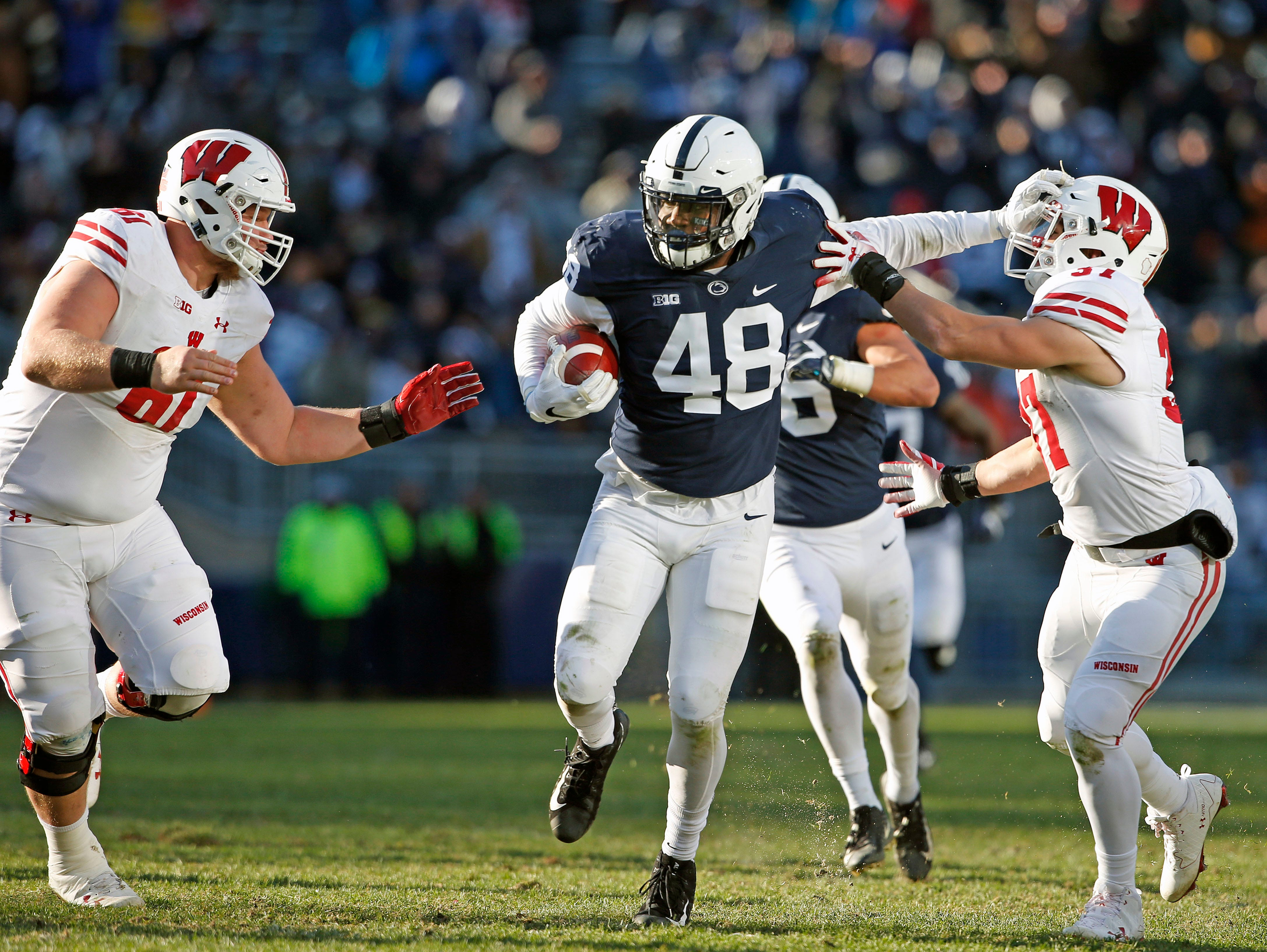 Penn State's Shareef Miller (48) stiff arms Wisconsin's Garrett Groshek (37) after intercepting a pass during the second half of an NCAA college football game in State College, Pa., Saturday, Nov. 10, 2018. Penn State won 22-10.