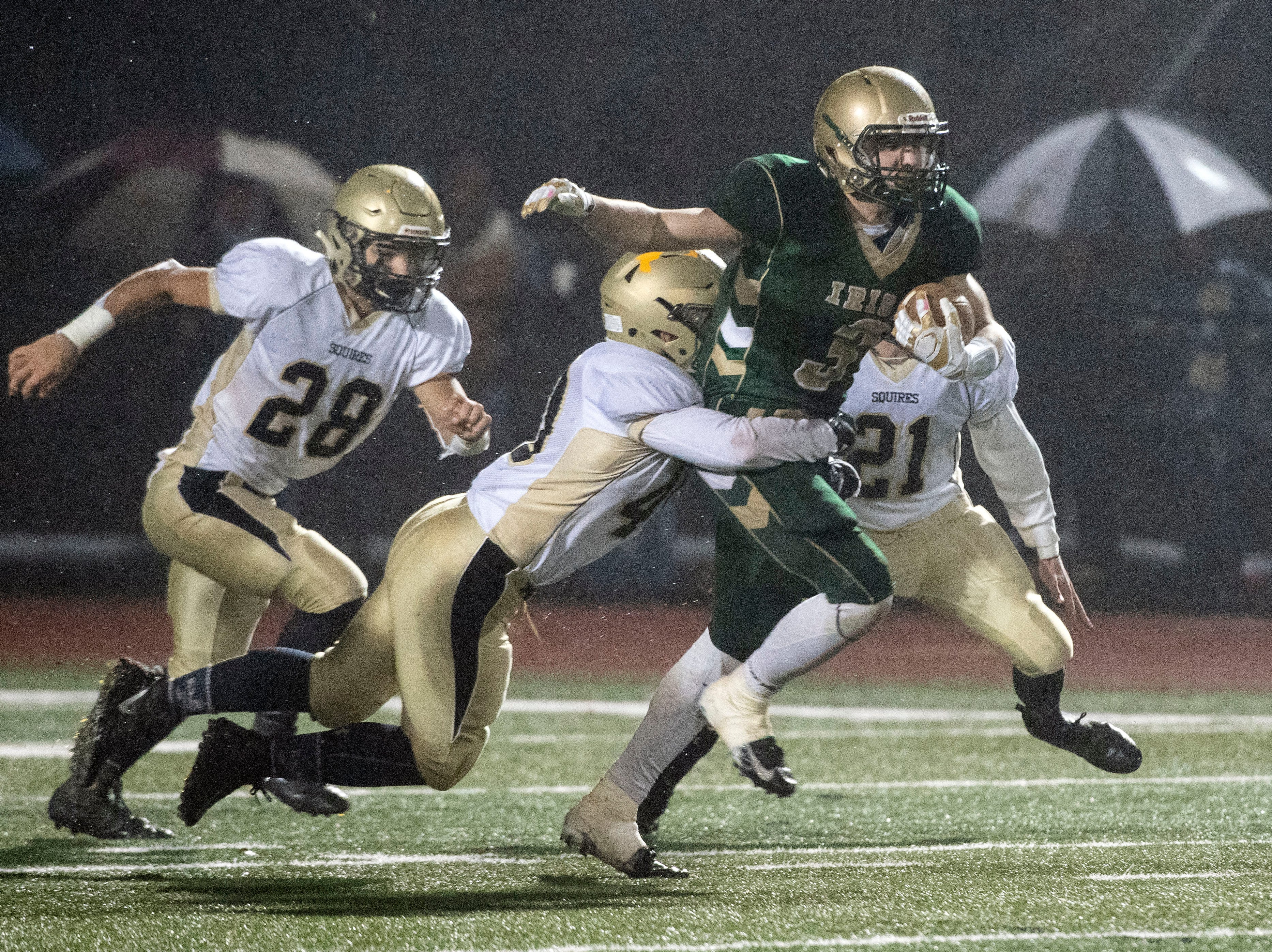 York Catholic's Cole Witman (3) runs the ball while a Delone Catholic defensemen wraps up a tackle during the District III 2A championship game at South Western High School on Nov. 9, 2018. The York Catholic Fighting Irish beat the Delone Catholic Squires in overtime, 28-21.