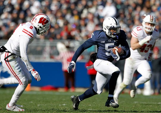 Penn State's Jahan Dotson (5) takes off running after a catch as Wisconsin's Deron Harrell (8) gives chase during the first half of an NCAA college football game in State College, Pa., Saturday, Nov. 10, 2018.