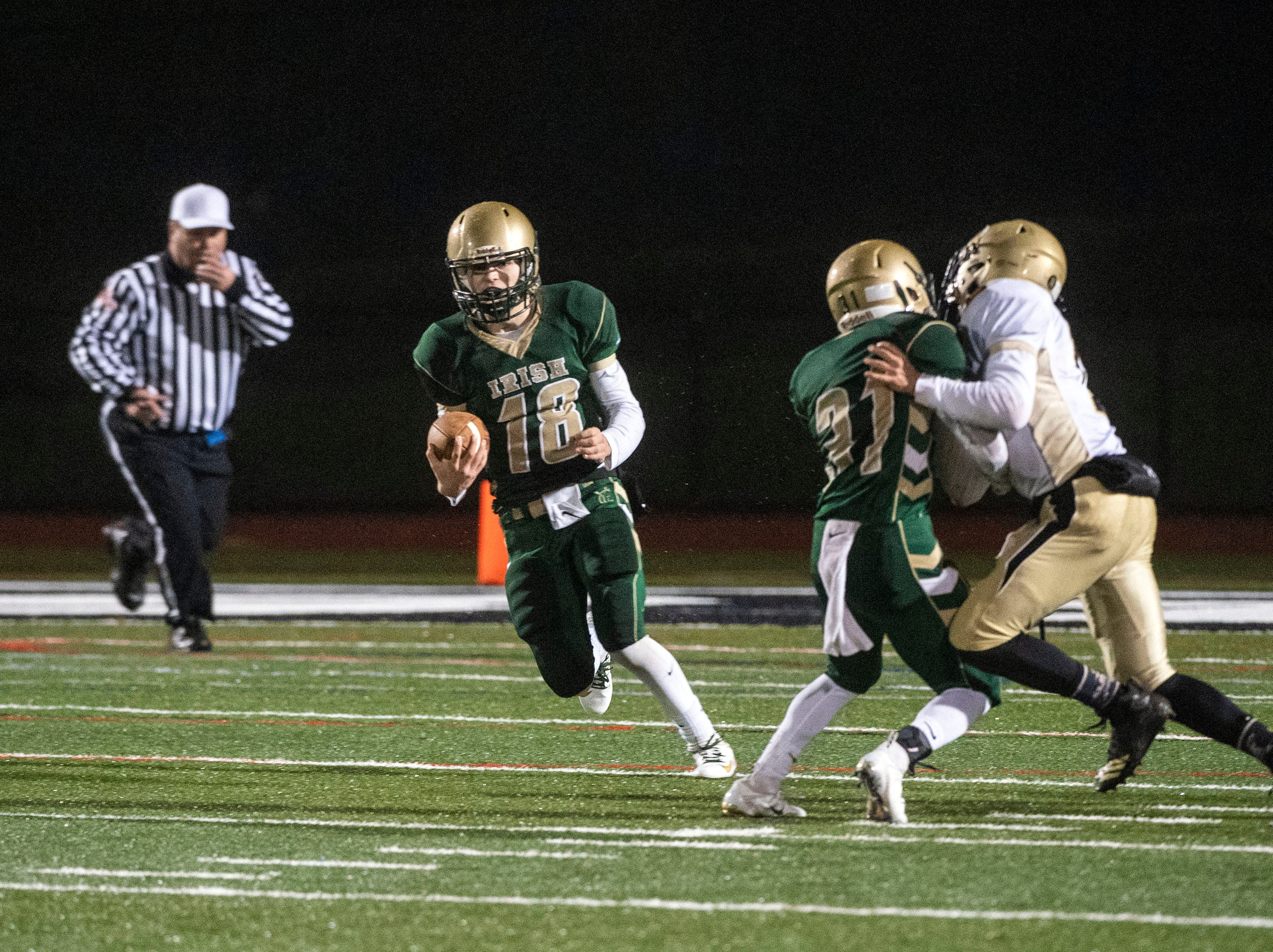 York Catholic quarterback Wesley Burns (18) runs the ball down the field during the District III 2A championship game at South Western High School on Nov. 9, 2018. The York Catholic Fighting Irish beat the Delone Catholic Squires in overtime, 28-21.
